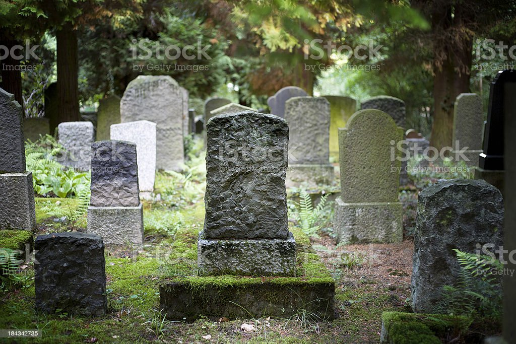 Rows of very old and weathered tombstones stock photo
