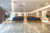istock Rows of vintage blue chairs on beige glossy marble floor in modern light hall interior of luxury office building. Auditorium background with copy space 1242127035