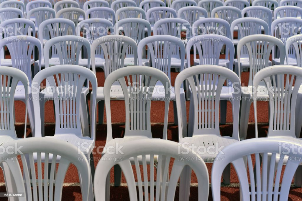 Rows of white folding chairs on lawn before a graduation ceremony in summer time stock photo
