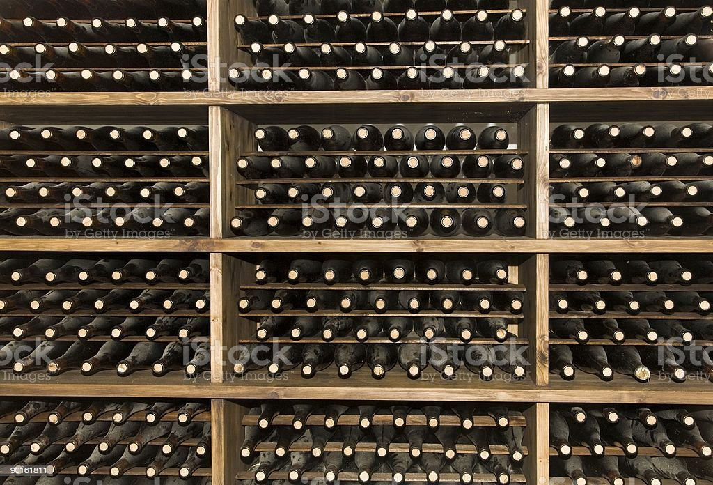 Rows of wine bottles stacked in a wine cellar royalty-free stock photo