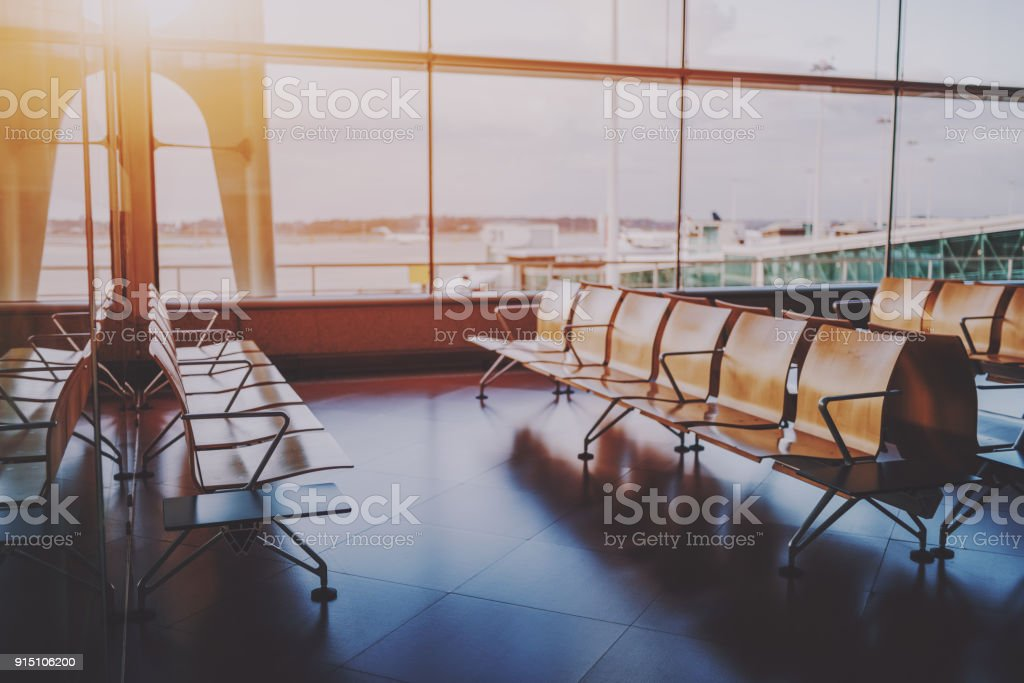 Rows of wooden seats near airport gate stock photo