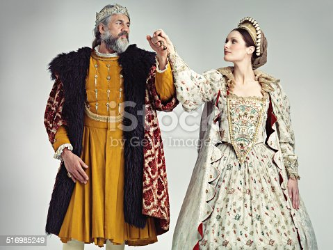 Studio portrait of a king and queen standing hand in hand