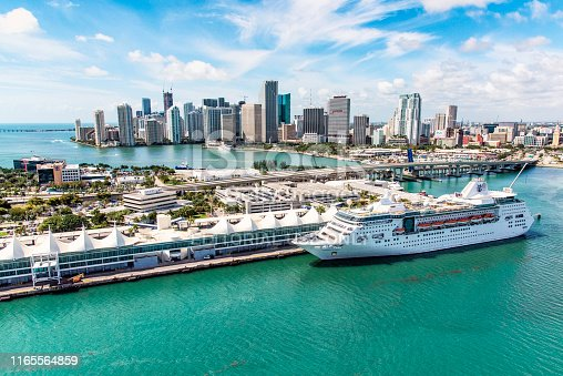 Miami, United States - March 9, 2017:  A large Royal Caribbean cruise-line ship docked at the terminal with downtown Miami, Florida rising in the background.