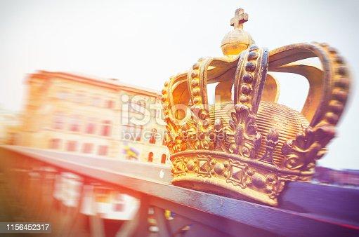 Gold coloured royal crown on bridge Skeppsholmsbron between Ostermalm and Skeppsholmen districts in central Stockholm, Sweden.
