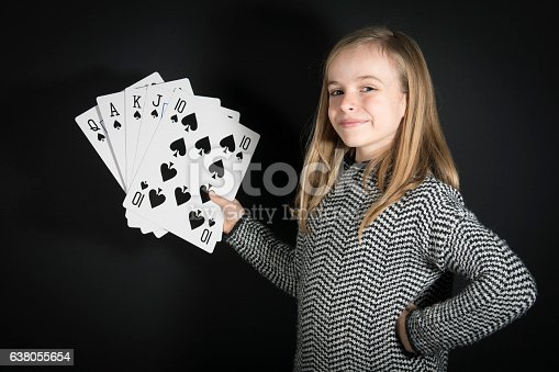 A smart blonde little girl (10 Y old) is holding in her hands five giant cards, they are spades and make a royal flush. Black background.