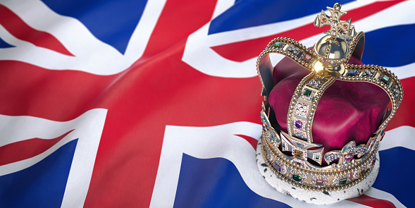 istock Royal golden crown with jewels on british  flag. Symbols of UK United Kingdom. 1128524207