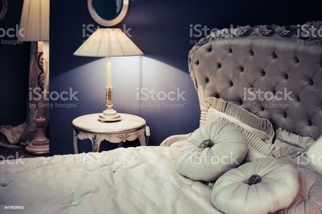 koninklijke interieur van luxe slaapkamer bed met zijdeachtige hoofdeinde en mooie linnen klassieke lichter