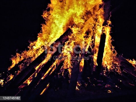 Isolated Photograph of a Very Large Bonfire Burning - Flames - Sparks, Smoke, and Heat from Burning Fire - Set Afire - Major Fire Burning - Super Big Bonfire - Flames are Shooting High into the Air - The Fire is Lit - Wood Pile Burns in the Yard - Engaging Photo of Large Pile of Burning Wood