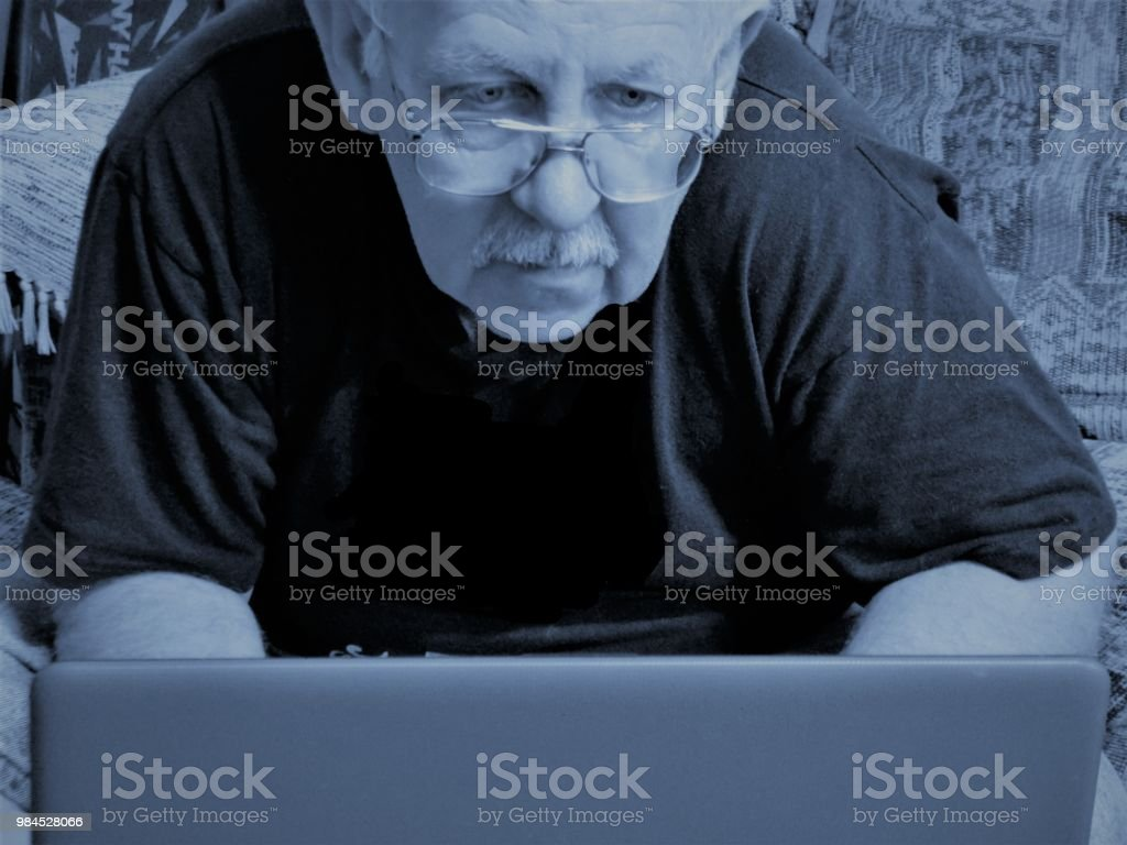 Royalty Free Photograph - Senior Adult is Working at the Laptop Computer - Man Seriously Engrossed with the Daily Internet Content - Checking Email - Older Man watches Latest Videos on his Computer - Online Again stock photo
