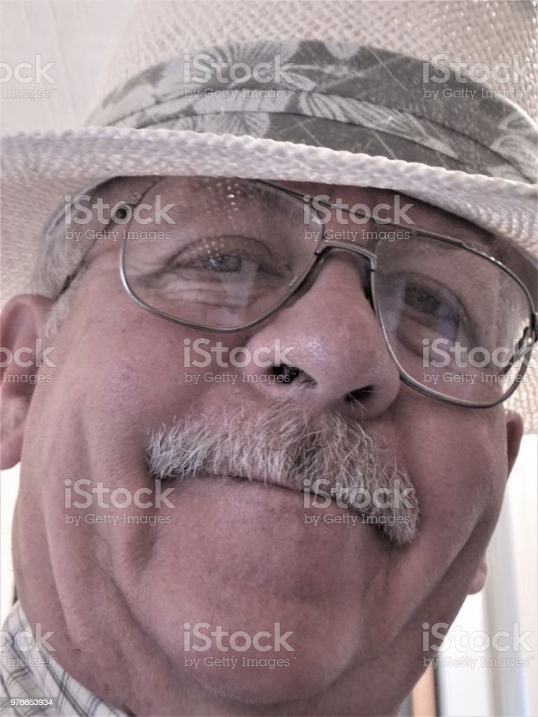 Royalty Free Photograph - Wearing my White Colored Summer Hat - Attractive Smiling Older Man with Mustasche Looking at Camera Lens - Head Shot Portrait of Man wearing Glasses - Happy Man on Vacation - Very Joyful Smile on Mature Male - Close Up Portrait stock photo