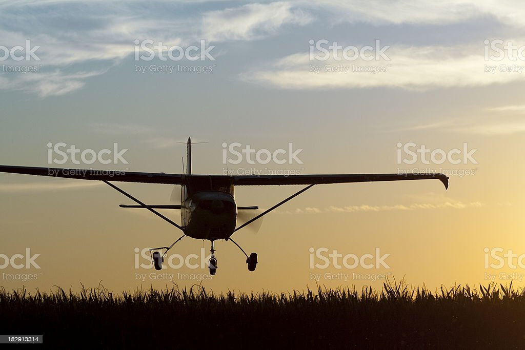 Royalty Free Stock Photo: Low Flying Cessna Airplane at Sunset stock photo