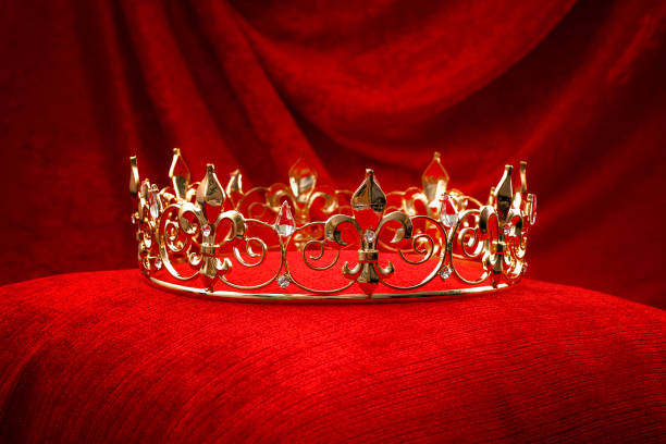 Royalty, monarch coronation or leadership conceptual idea with king gold crown with jewels on red velvet pillow Royalty, monarch coronation or leadership conceptual idea with king gold crown with jewels on red velvet pillow aristocrat stock pictures, royalty-free photos & images