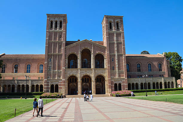 Royce Hall at the University of California Los Angeles  (UCLA) Los Angeles, California, USA - July 9. 2015: A group of studens walk past Royce Hall at the Univrsity of California, Los Angeles (UCLA) campus. westwood neighborhood los angeles stock pictures, royalty-free photos & images