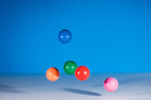 5 multicolor rubber balls in mid air against a blue background