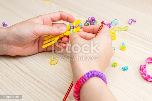 Rubber Band Weaving. Knitting rubber bands with loom knit. Hands of girl weaving wristband of rubber bands.