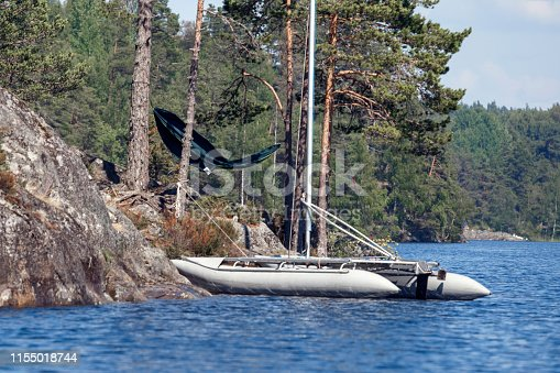 rubber boat off the rocks on forest background
