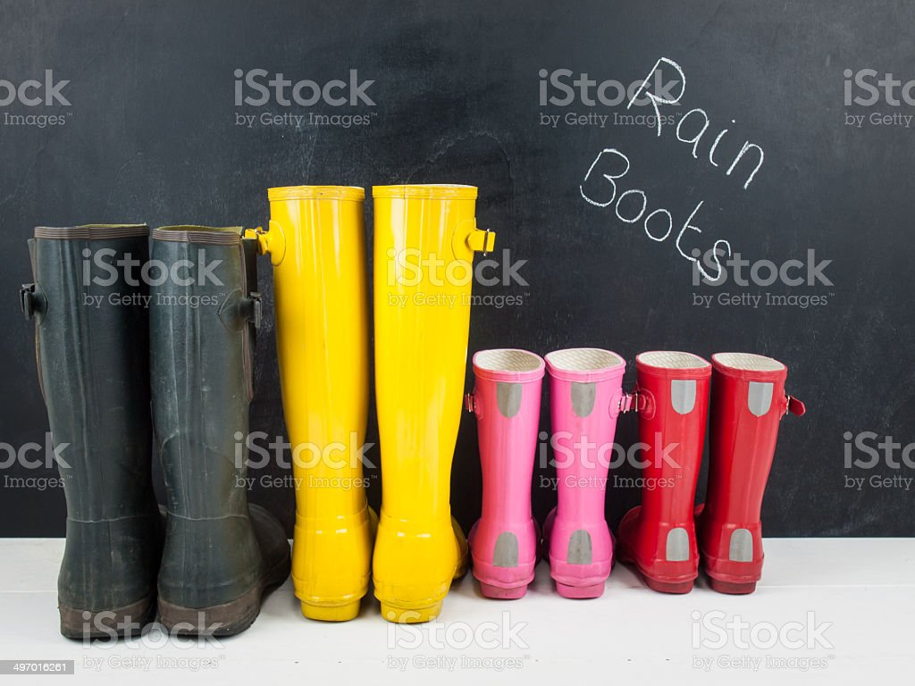 rubber boots against a blackboard stock photo