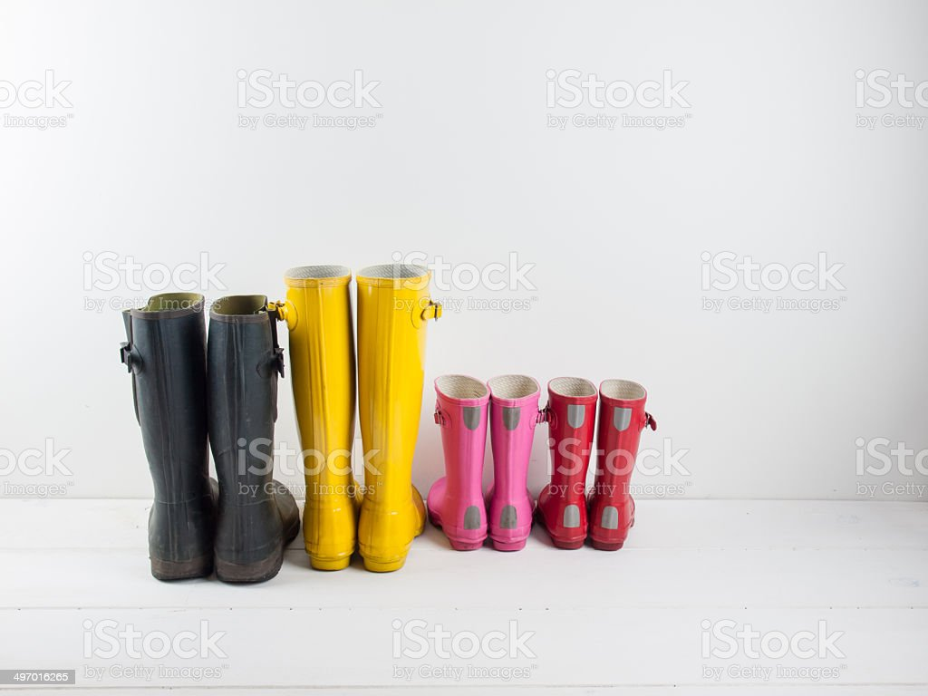 rubber boots against a white wall stock photo