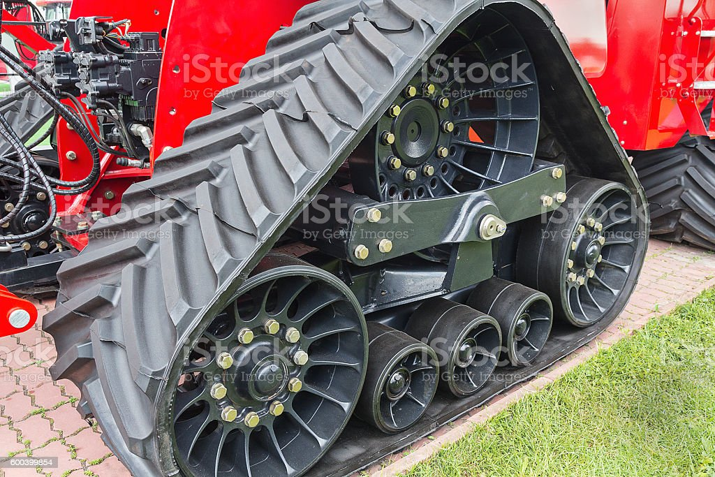 Rubber caterpillar farm tractor close up. Industry stock photo
