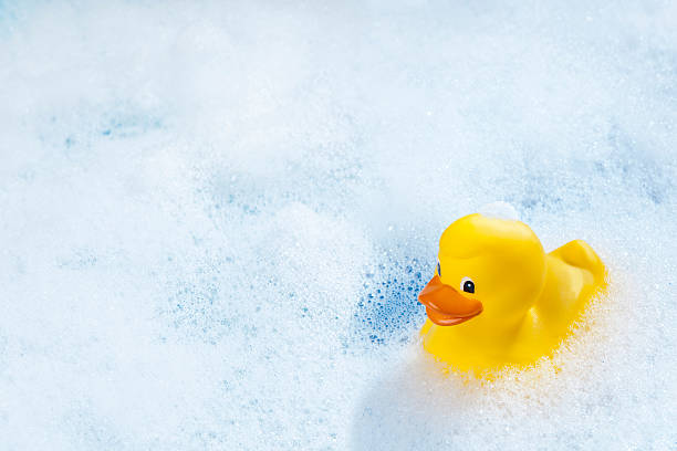 Rubber duck A yellow rubber duck in bathtub. bubble bath stock pictures, royalty-free photos & images