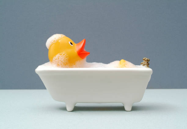 Rubber duck relaxing in the bath giant rubber duck taking a bath. grey background bubble bath stock pictures, royalty-free photos & images