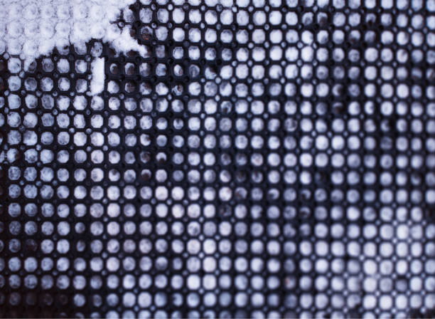 Rubber entrance mat filled with snow bokeh texture stock photo