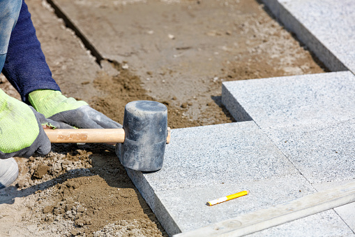 The hands of a working bricklayer hold a rubber hammer and lay granite paving slabs on a sandy base on a sunny day. Close-up, selective focus, copy space.