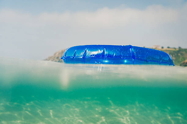 rubber ring floating on sea surface on a bright day - rubber ring stock photos and pictures
