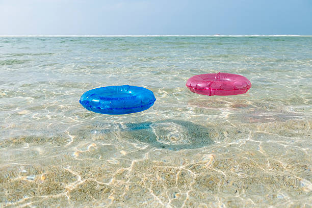 rubber rings floating in the clear sea, pedn vounder cornwall - rubber ring stock pictures, royalty-free photos & images