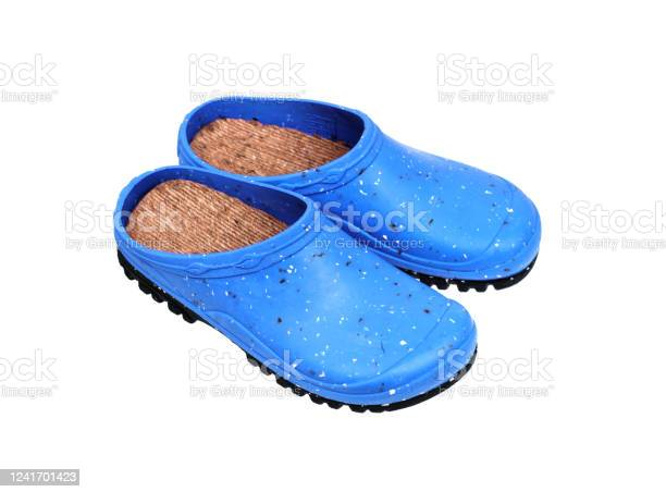 Photo of Rubber shoes isolate on a white background. Colored rubber slippers on a tractor sole. Shoes for the garden, beach and housework.