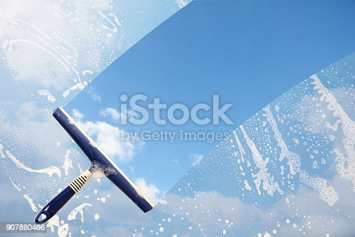 istock Rubber squeegee cleans a soaped window and clears a stripe of blue sky with clouds, concept for tranparency or spring cleaning, copy space in the background 907860466