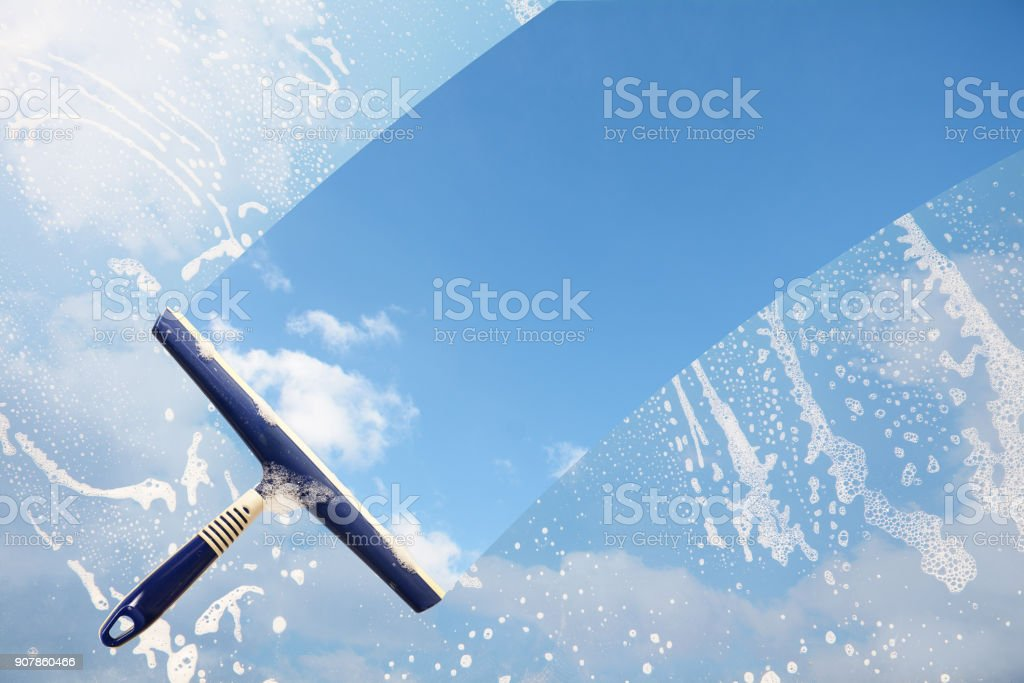 Rubber squeegee cleans a soaped window and clears a stripe of blue sky with clouds, concept for tranparency or spring cleaning, copy space in the background stock photo