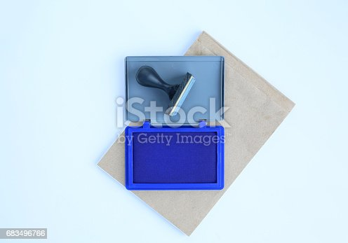 683496662 istock photo Rubber stamp and Blue Ink cartridges on brown book against white background. 683496766