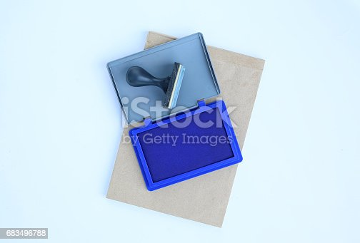 683496662 istock photo Rubber stamp and Blue Ink cartridges on brown book against white background. 683496788