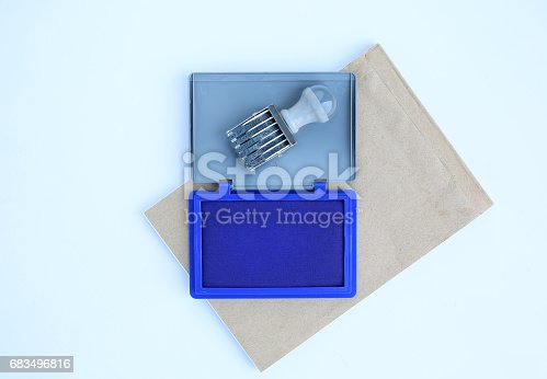 683496662 istock photo Rubber stamp and Blue Ink cartridges on brown book against white background. 683496816