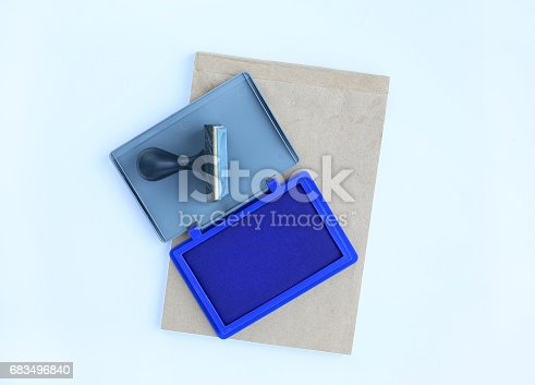 683496662 istock photo Rubber stamp and Blue Ink cartridges on brown book against white background. 683496840
