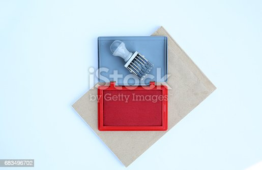 683496662 istock photo Rubber stamp and Red Ink cartridges on brown book against white background. 683496702