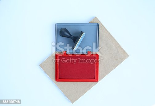 683496662 istock photo Rubber stamp and Red Ink cartridges on brown book against white background. 683496748