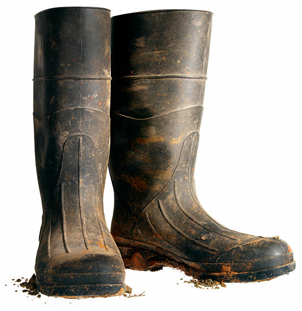 Rubber Work Boot, Isolated Hard working black rubber boots covered in dirt against a white background. burwellphotography stock pictures, royalty-free photos & images