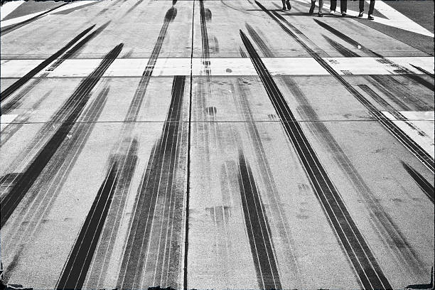 Rubbings on an airport runway Tire tracks and marks at the end of an airfield. Manipulated black and white film retro look. tire track stock pictures, royalty-free photos & images