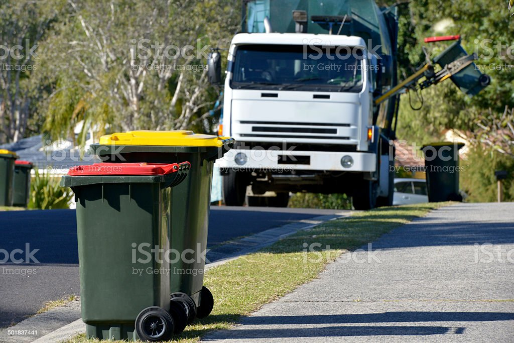 Rubbish bins with rubbish truck in background lifting a bin stock photo