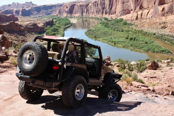 rubicon jeep op de moab rim trail met uitzicht over de colorado rivier. - moab utah stockfoto's en -beelden