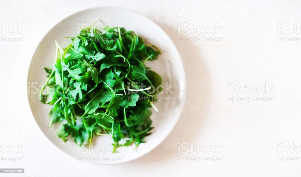 Ruccola leaf salad on white background with copyspace stock photo