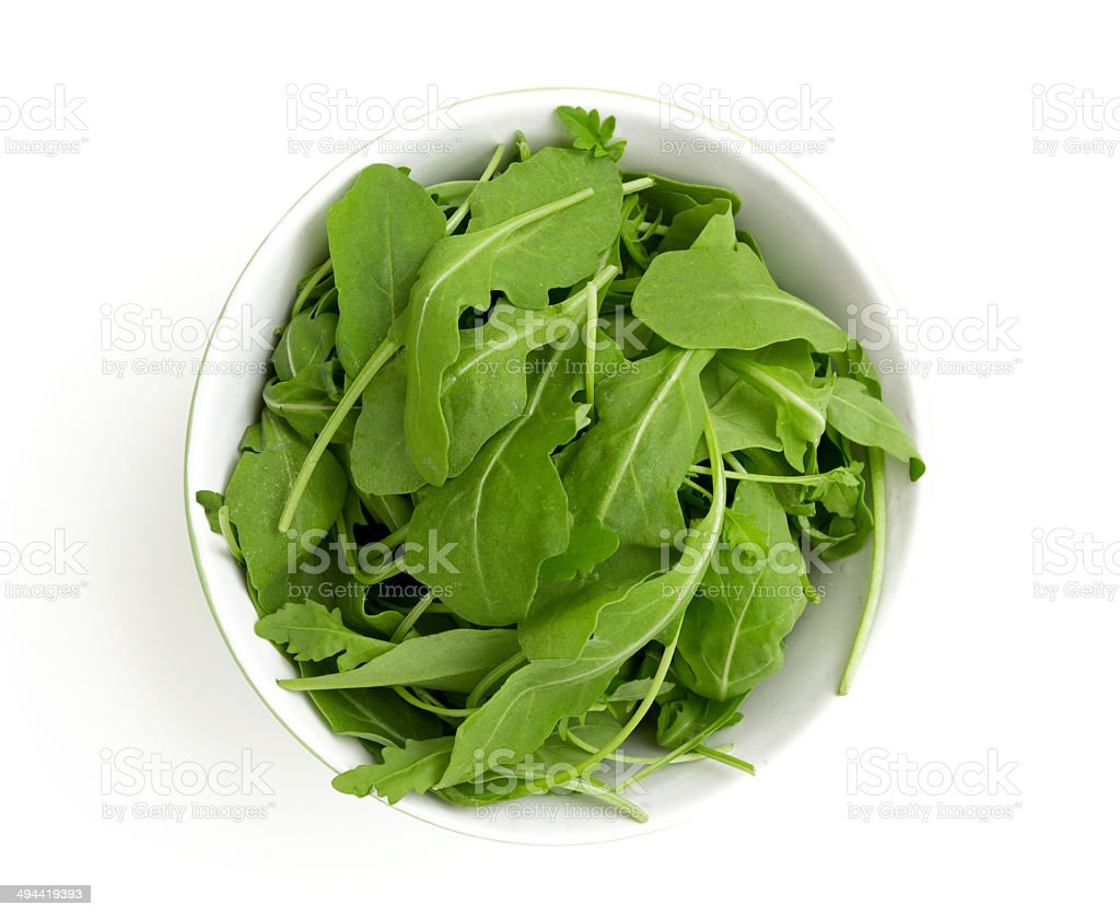 rucola in a glass bowl isolated on white background stock photo
