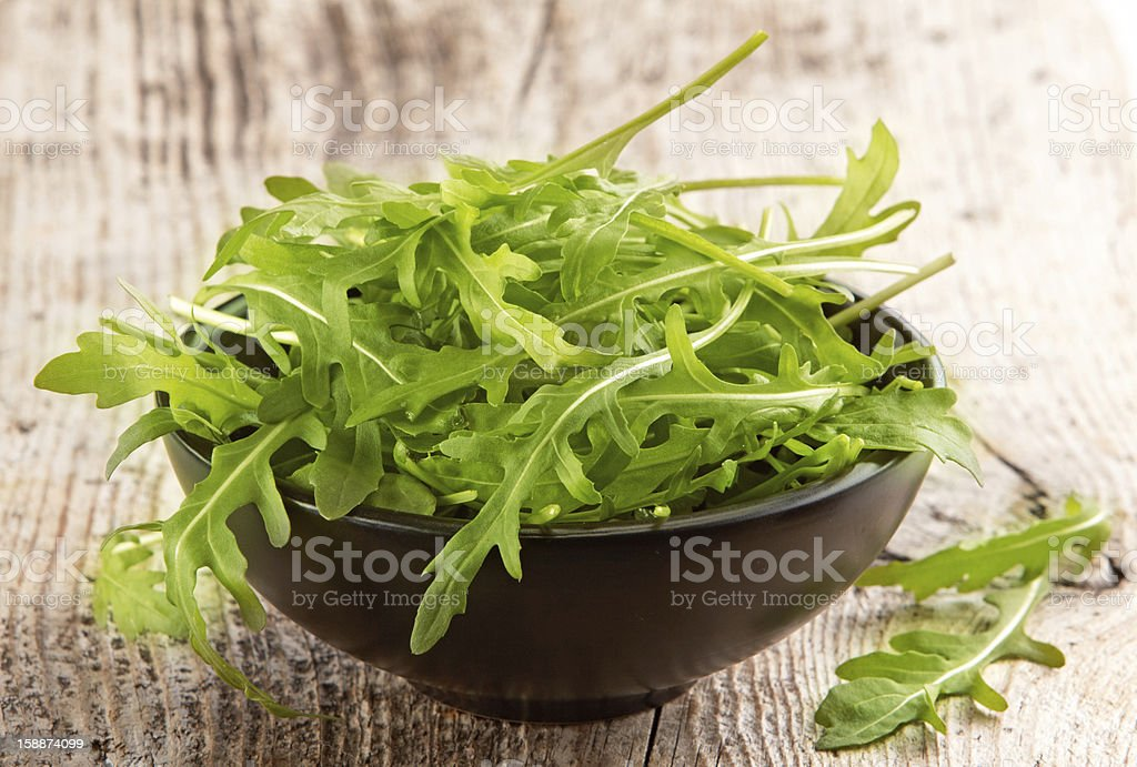 Rucola in black bowl stock photo