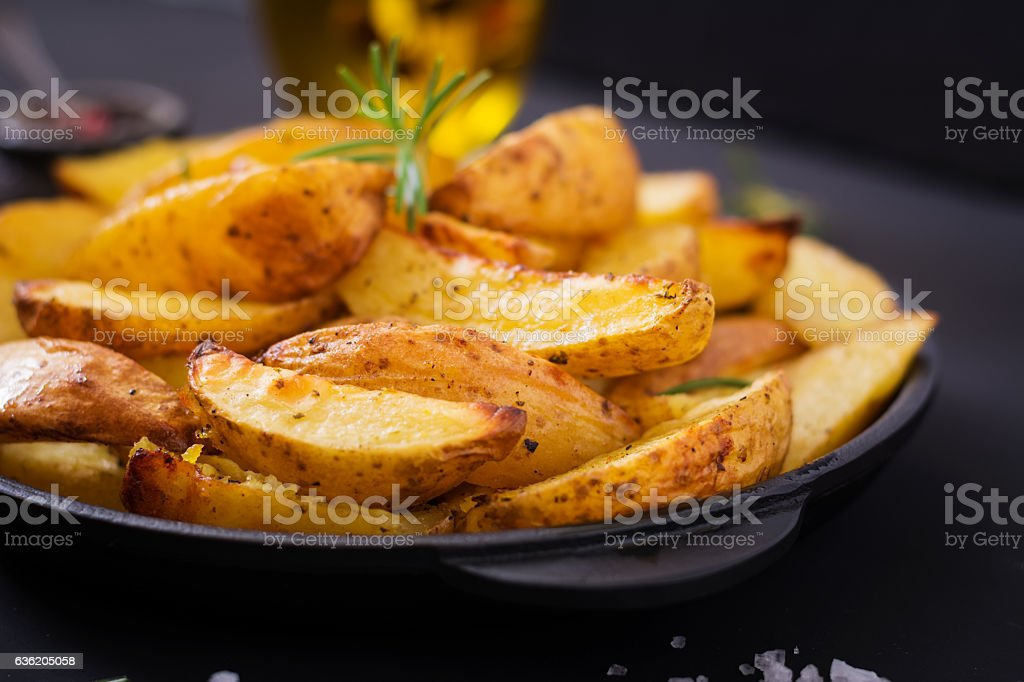 Ruddy Baked potato wedges with rosemary and garlic stock photo
