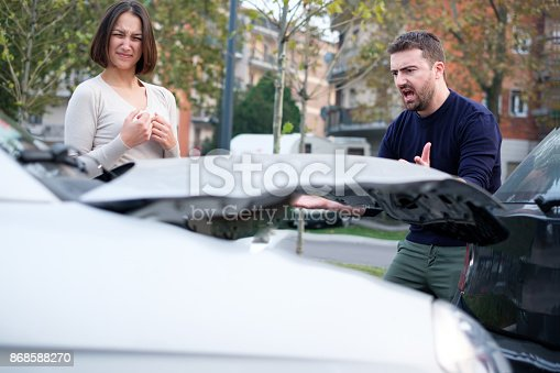 1047083324 istock photo Rude angry man having a quarrel with woman after car crash 868588270