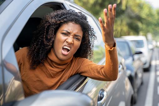 Aggressive woman driving car shouting at someone