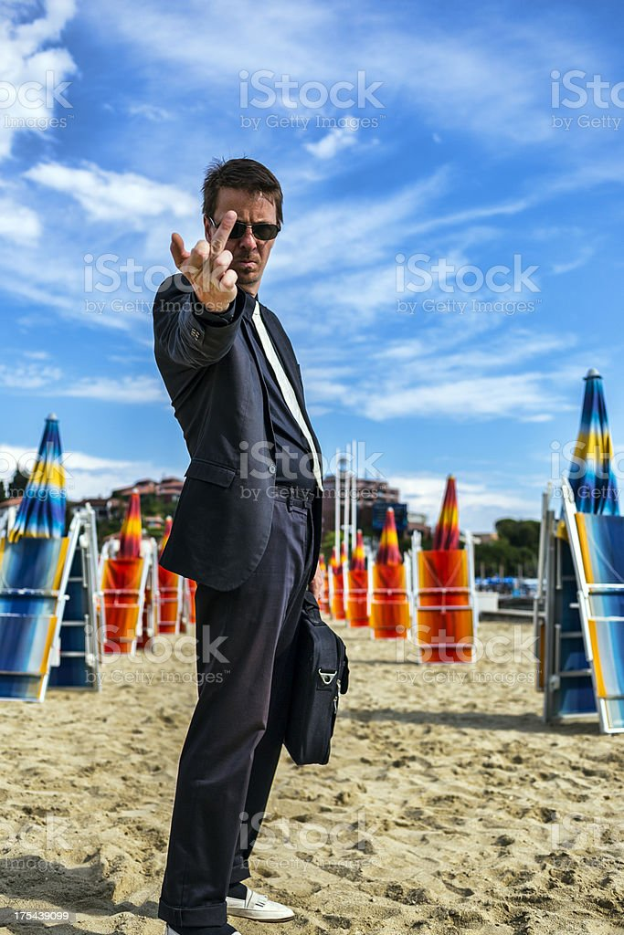 Rude businessman giving up everything on the beach stock photo