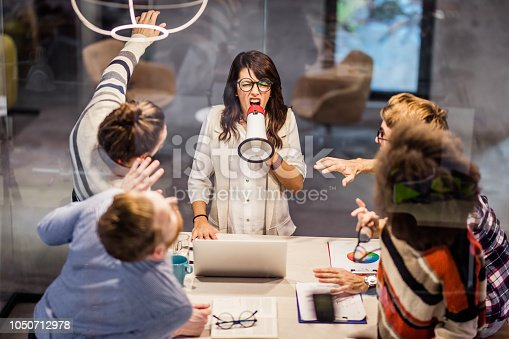 463813207 istock photo Rude female leader yelling at her coworkers through megaphone in the office. 1050712978
